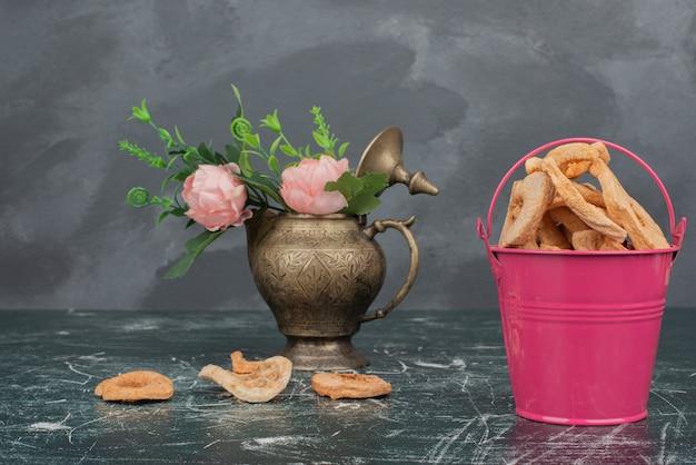 Petit bouquet avec assiette en bois de fruits secs sur mur de marbre.