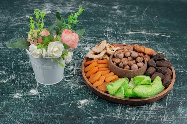 Petit bouquet avec assiette en bois de fruits secs sur une surface en marbre.