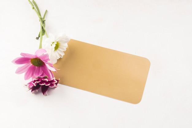 Petit bouquet avec carte-cadeau posée sur un bureau blanc