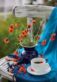 Un petit bouquet de coquelicots rouges dans un vase bleu sur une chaise vintage.
