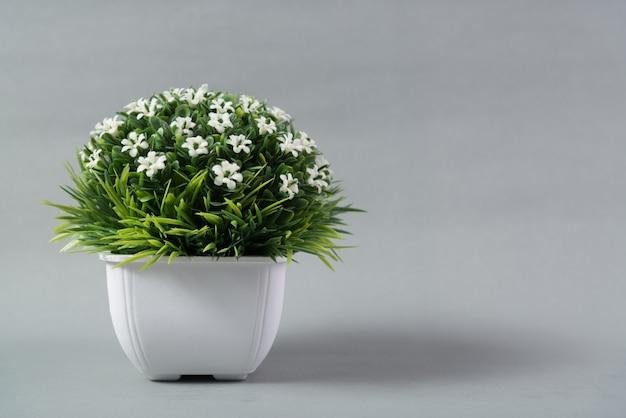 Petit bouquet décoratif d'arbres et de fleurs dans un vase blanc sur fond gris