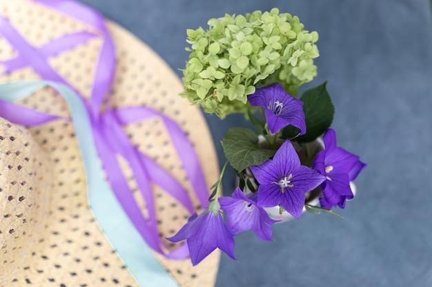 Petit bouquet d'hortensias verts et de cloches à côté du chapeau de paille de la femme sur fond bleu foncé. concept de vacances d'été. image pour blog ou publicité. mise au point sélective