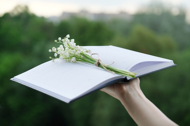 Petit bouquet de muguets avec corde artisanale dans un cahier ouvert à la main de la femme