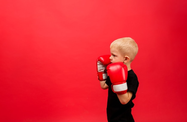 Petit boxeur en gants de boxe rouges se tient sur le côté dans un stand sur le rouge