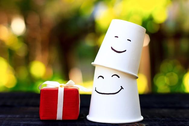 Petit cadeau rouge attaché avec un ruban blanc et l'émotion de joie, de plaisir