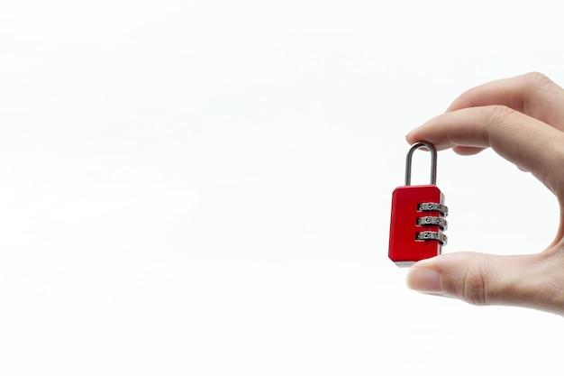 Petit cadenas rouge à la main sur fond blanc. main tenant une petite serrure à combinaison. sécurité