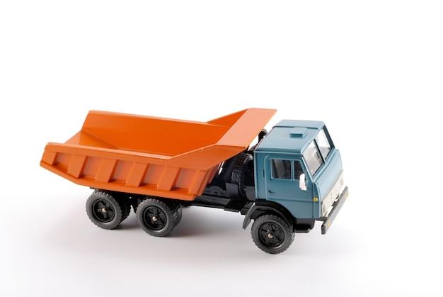 Un petit camion à benne basculante sur un fond blanc en métal