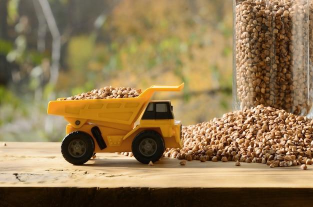 Un petit camion-jouet jaune est chargé de grains bruns de livrée de sarrasin