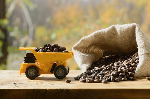 Un petit camion jouet jaune est chargé de grains de café bruns