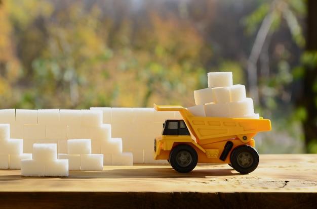 Un petit camion-jouet jaune est chargé avec des morceaux de sucre blanc près du mur de sucre.