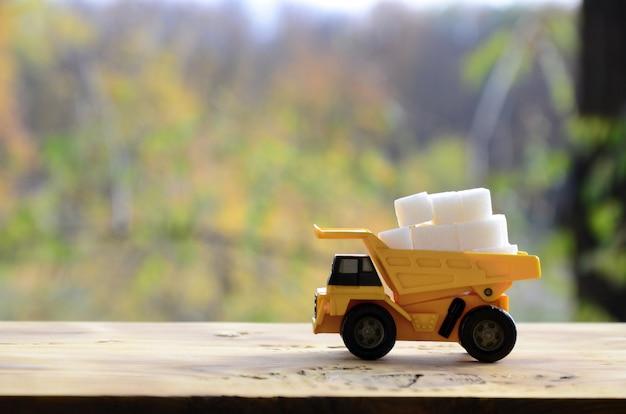 Un petit camion-jouet jaune est chargé de morceaux de sucre blanc.