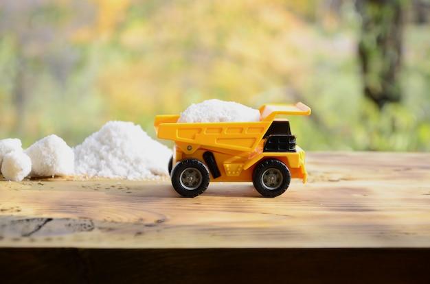 Un petit camion-jouet jaune est chargé avec une pierre de sel blanc à côté d'un tas de sel.