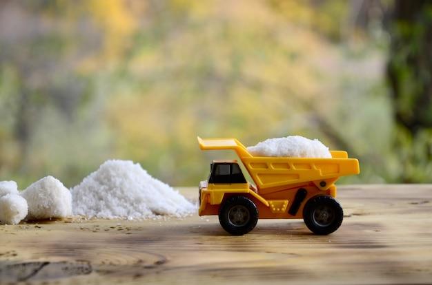 Un petit camion jouet jaune est chargé avec une pierre de sel blanc à côté d'un tas de sel