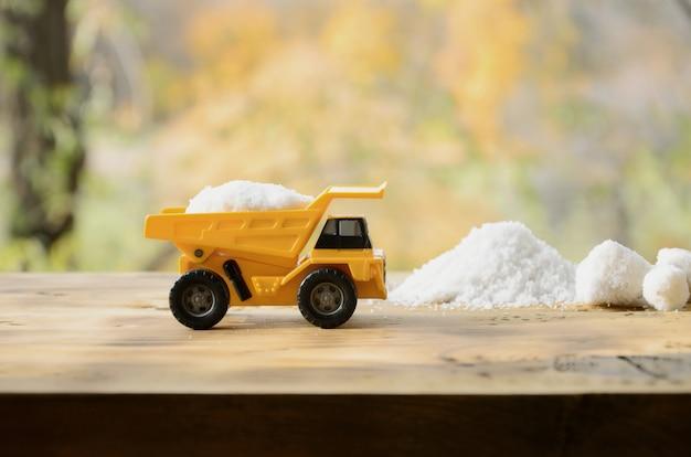 Un petit camion jouet jaune est chargé avec une pierre de sel blanc