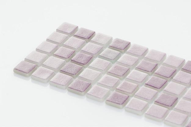 Petit carreau de céramique violet sur fond blanc, majolique. pour le catalogue