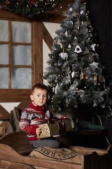 Petit chandail de noël pour enfant détient un cadeau de noël alors qu'il est assis à côté d'un arbre de noël décoré