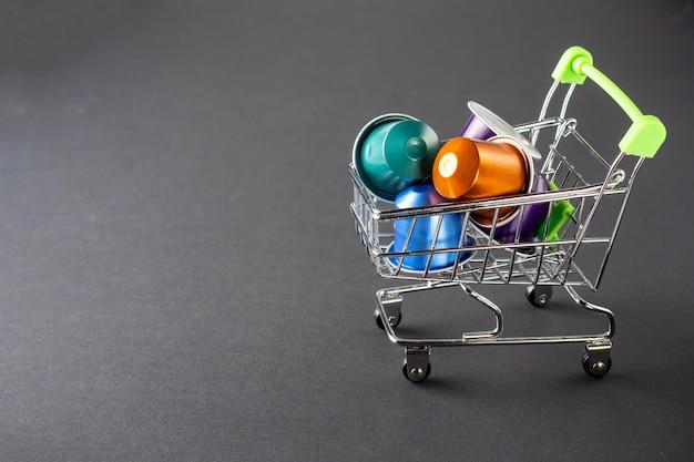 Un petit chariot d'épicerie plein de capsules en aluminium colorées remplies de café moulu aromatique