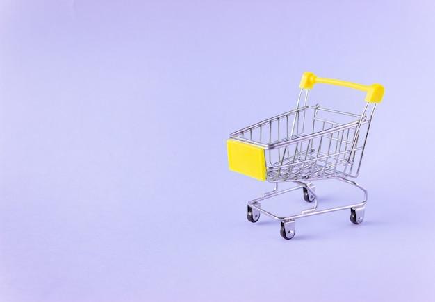 Un petit chariot d'épicerie sur violet