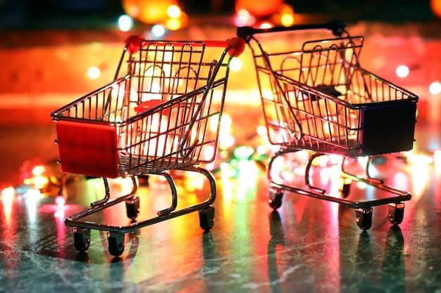 Petit chariot de supermarché en métal sur fond de lumières colorées