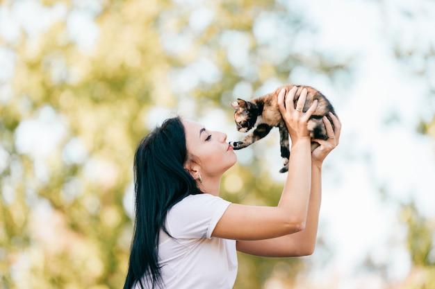 Le petit chat a mis sa patte sur les lèvres de la femme.