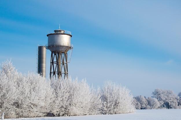 Petit château d'eau de ville, éclairé par la lumière du soleil sur un paysage gelé.