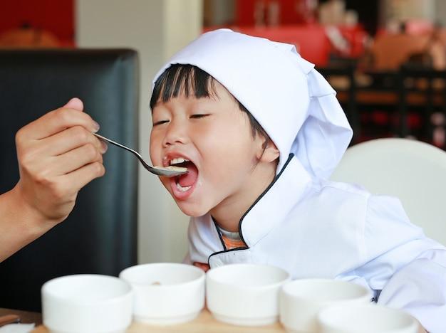 Petit chef apprend à manger des plats savoureux.