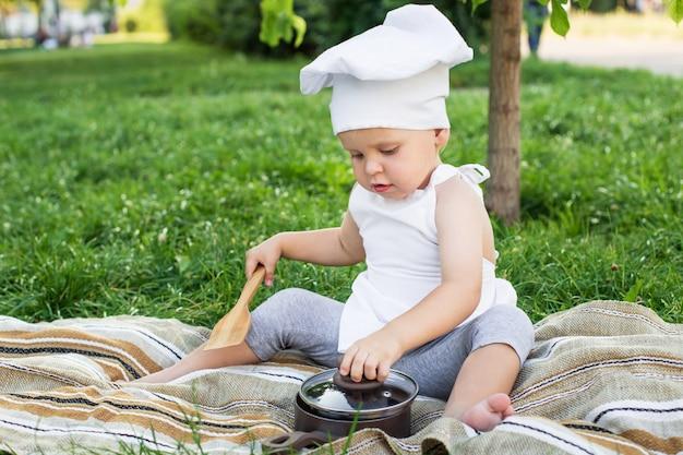 Petit chef cuisine et mange des pâtes sur un pique-nique en plein air
