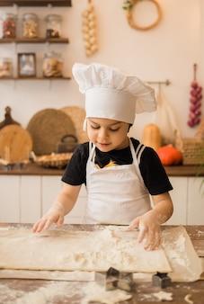 Petit chef dans un tablier blanc et une casquette pétrit la pâte avec ses mains dans la cuisine
