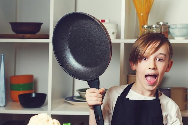 Petit chef drôle avec une casserole dans la cuisine. garçon portant un tablier de chef. enfant rêvant d'un futur métier. enfant aux cours de cuisine