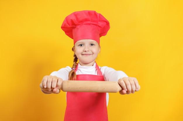 Petit chef de fille tenant un rouleau à pâtisserie.