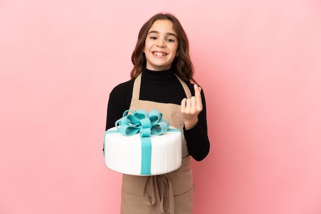 Petit chef pâtissier tenant un gros gâteau isolé sur fond rose faisant un geste d'argent