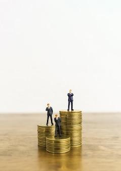 Petit chiffre miniature homme d'affaires se tenir sur des piles de pièces de monnaie.