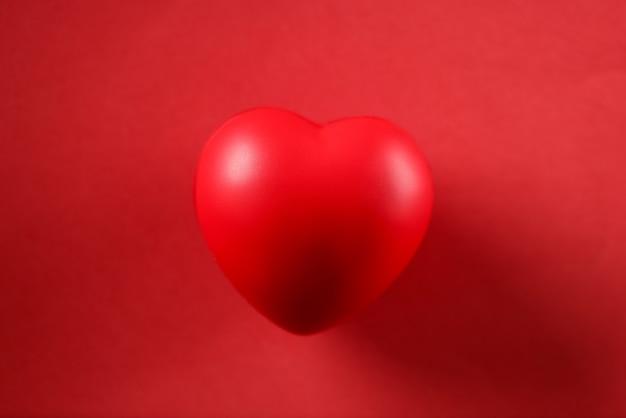 Petit coeur de jouet couché sur une maquette de gros plan de fond rouge. concept de la saint-valentin