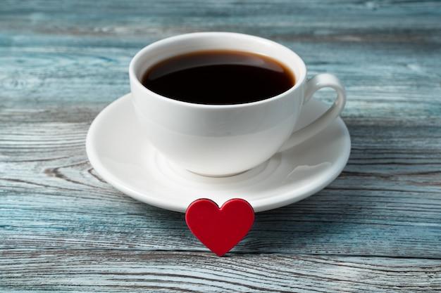 Un petit coeur rouge est appuyé contre une tasse de café sur une soucoupe sur un fond en bois.