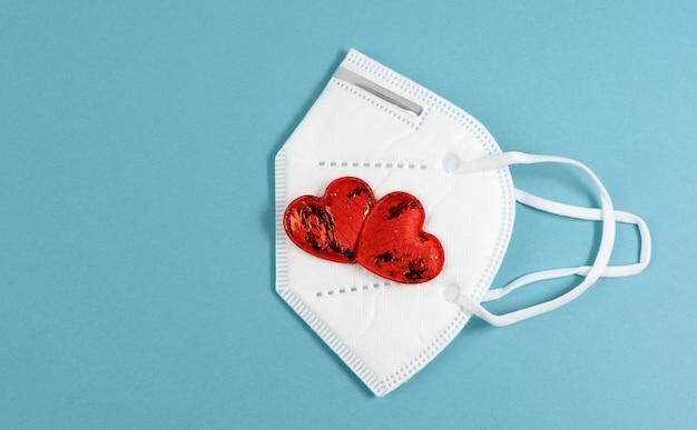 Petit coeur textile rouge se trouve sur un masque médical jetable blanc, fond bleu