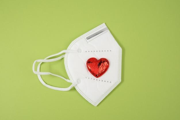 Petit coeur textile rouge se trouve sur un masque médical jetable blanc, surface verte