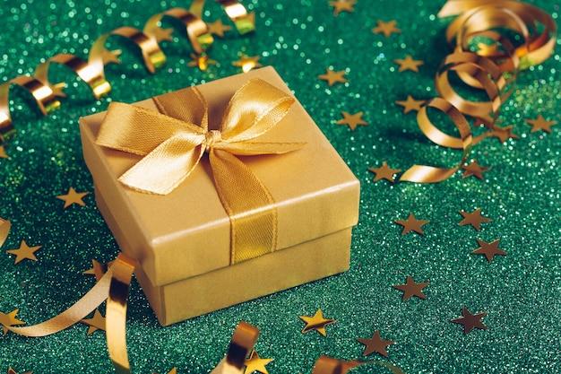 Petit coffret cadeau avec noeud doré sur fond vert pailleté