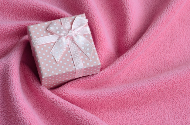Un petit coffret rose avec un petit noeud repose sur une couverture