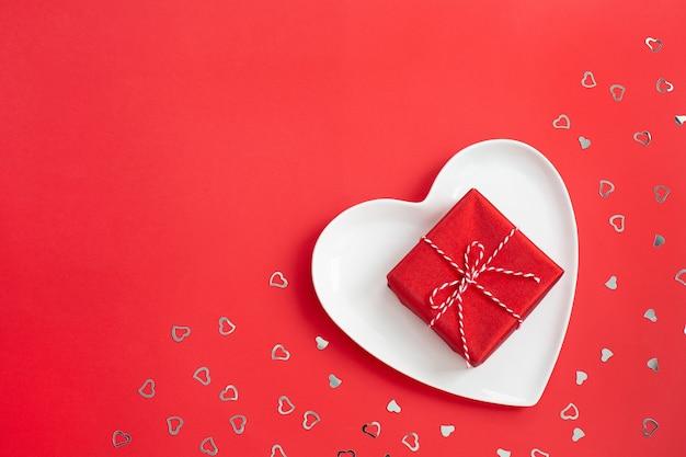 Petit coffret rouge sur une assiette blanche en forme de cœur.