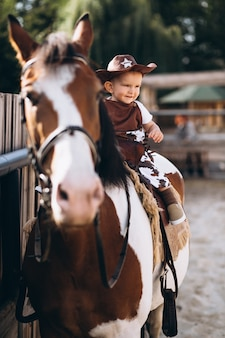 Petit cow-boy assis sur un cheval