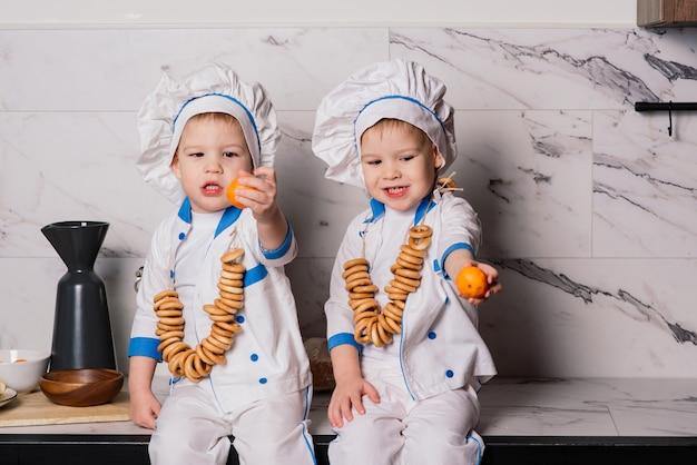 Petit cuisinier mignon avec des couverts assis sur une cuisine, frères jumeaux, mandarine, bagels