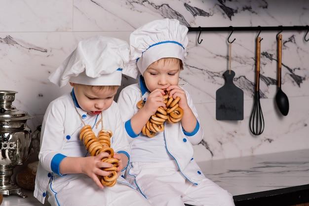 Petit cuisinier mignon avec des couverts assis sur une cuisine