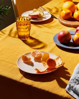 Petit-déjeuner alimentaire avec table de fruits couvrant une nappe en lin jaune vif ombre dure profonde du soleil