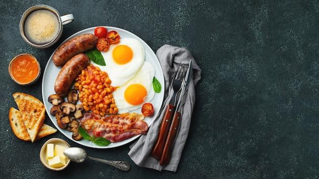 Petit-déjeuner anglais complet sur une assiette avec des œufs au plat, des saucisses, du bacon, des haricots, des toasts et du café. vue de dessus.