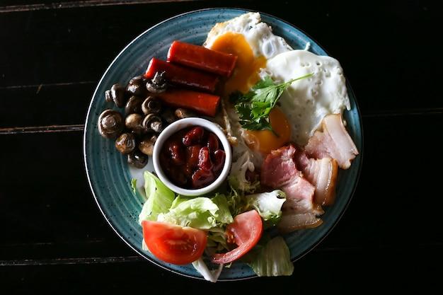 Petit déjeuner anglais complet avec bacon, saucisse, œuf au plat et fèves au lard