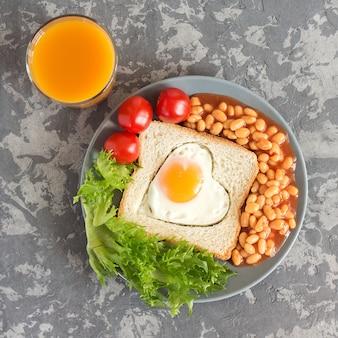 Petit déjeuner anglais complet avec œufs au plat, haricots, toasts, salade, tomates sur fond gris