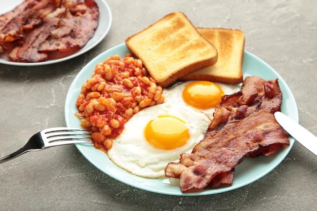 Petit-déjeuner anglais complet traditionnel: œufs au plat, haricots, bacon et pain grillé sur fond gris.