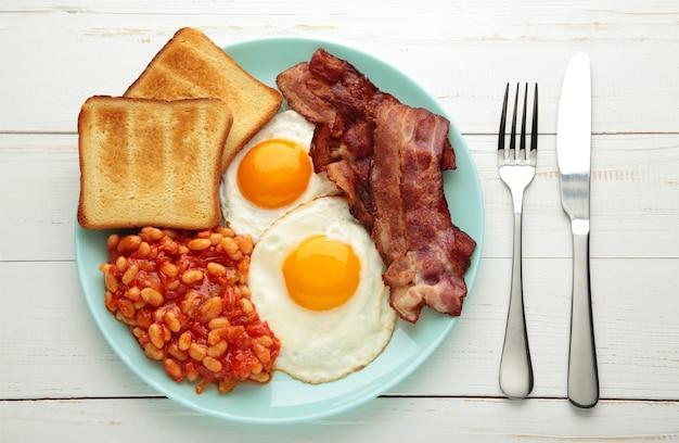 Petit-déjeuner anglais complet traditionnel oeufs au plat, haricots, bacon et pain grillé sur tableau blanc