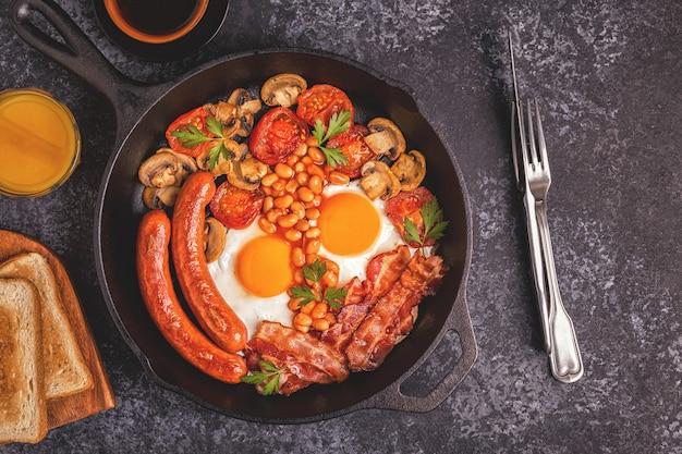 Petit-déjeuner anglais complet traditionnel avec œufs au plat, saucisses, haricots, champignons, tomates grillées et bacon. vue de dessus.