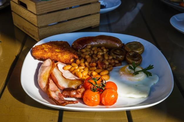 Petit-déjeuner anglais complet traditionnel avec œufs au plat, saucisses, haricots, champignons, tomates grillées et bacon.
